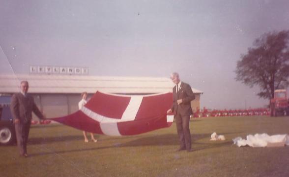 Ejer og grundlægger af Svogerslev Maskinfabrik, Georg Christiansen, hustruen, Nelly Christiansen og bogholder Mogens Bruun med flaget på jubilæums-dagen august 1970. Foto tilsendt af Mogens Bruun.